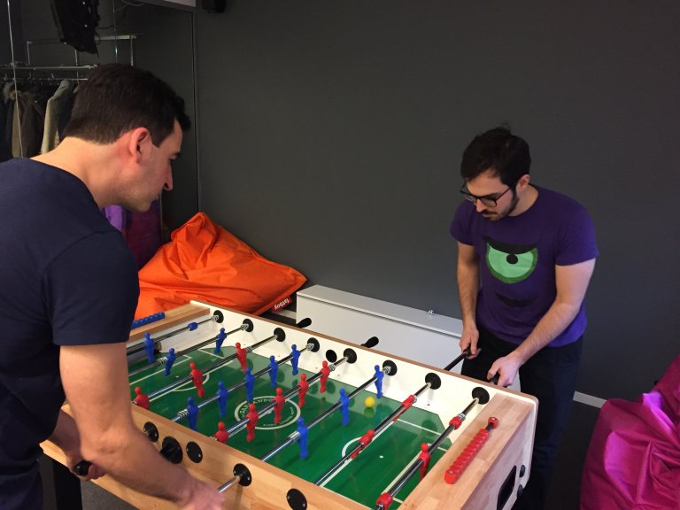 Two men playing Table Football in an office room